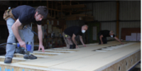 The Eden Insulation team fabricating an airtight insulated panel used in Passivhaus buildings